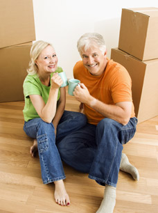 Consequences of Moving - Image of middle aged couple having coffee among moving boxes